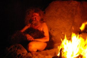 Prehistoric man looking at the fire
