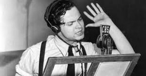 Orson Welles in front of the microphone, with raised hand, reading War of the Worlds