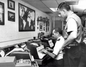 Senior Master Sgt. Luis Montanez and Major Michael Ennis of the U. S. Air Force, (left to right), at the operating position in the Washington Terminal of the Washington-Moscow Direct Communications Link known as the Hat Line.